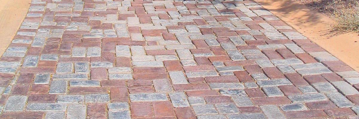 Installation - Stone and Brick Patio Pavers In a Backyard Leading up to a Brick Paver Staircase