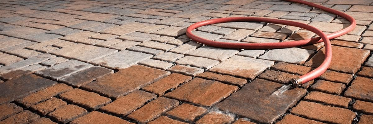 Pavers Vs. Concrete - Outdoor Brick Patio Pavers with a Hose Laid on Top of Them